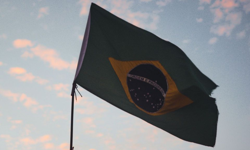 Brazilian flag against light blue sky filled with pink clouds