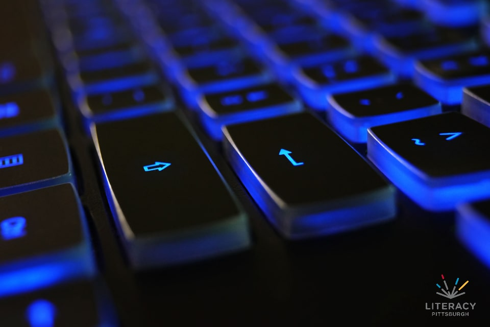 A computer keyboard backlit in blue
