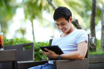 Man sitting outside, smiling at a tablet in his arms