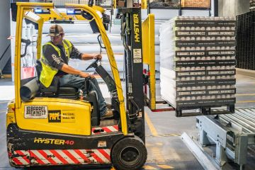 A forklift driver moves pallets