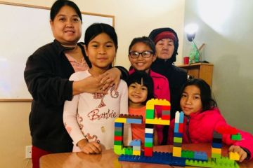 Family of six with a colorful children's block tower